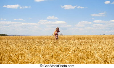 beautiful girl on a sunny day goes into the wheat field