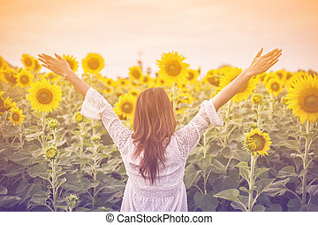 Beautiful girl on a vintage, field of sunflowers in pastel...