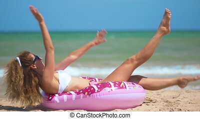Beautiful girl on inflatable donut dancing against the sea....