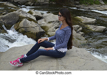 beautiful girl on the bank of a mountain river