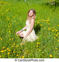 Beautiful girl on the field of dandelions is happy and enjoys the sun. sexy blonde in the spring