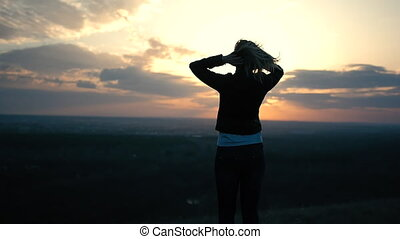 Beautiful girl on the sunset background