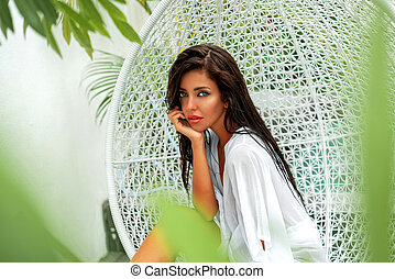 Beautiful girl on vacation. Fashion photo of a beautiful girl in the swing with decorations. Chic pool in a luxury villa.