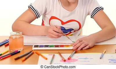 Beautiful girl paints color a stripes paper on white background, slow motion