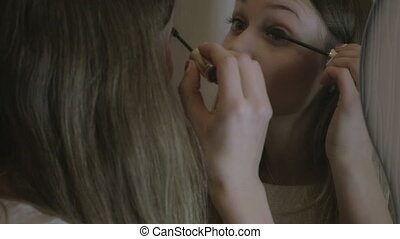 Beautiful girl paints the lashes mascara in front of mirror.