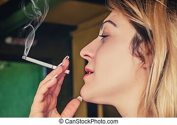 Beautiful girl pensive with her cigarette