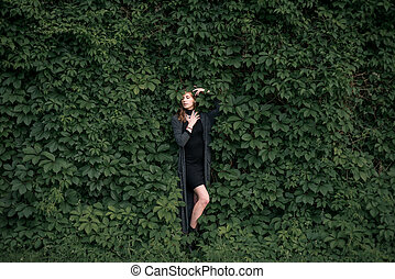 beautiful girl photographed against a garden wall