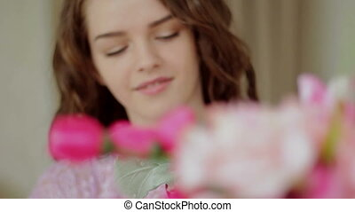 Beautiful girl picking flowers in a bouquet. Close-up
