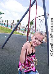 Beautiful girl play outdor on swing