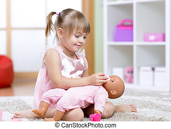 Beautiful girl playing doctor with a doll