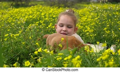 Beautiful girl playing on green grass with a puppy