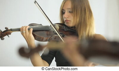 Beautiful girl playing the violin standing in front of a mirror