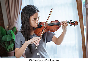 beautiful girl playing violin with violin bow