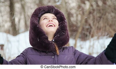 Beautiful girl playing with snow in winter
