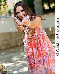 Beautiful girl playing with water in the garden. - Portrait...