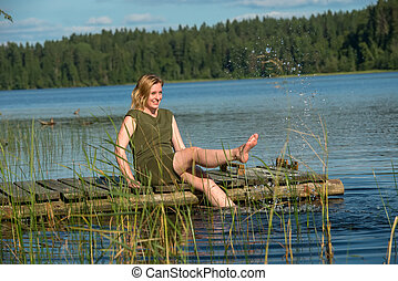 Beautiful girl plays with water sitting on a wooden jetty at a lake