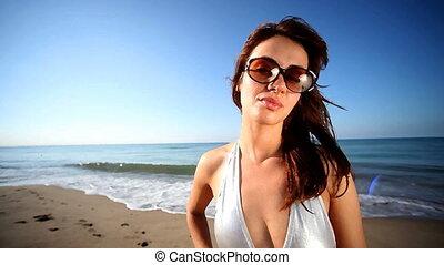 beautiful girl poses on the beach in a bikini at sunrise, barcelona, spain