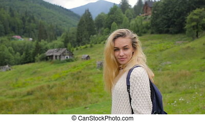 Beautiful girl posing at the camera and smiling on a background of forest and mountain village