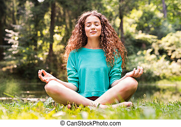 Beautiful girl practices yoga in the morning forest. - ...