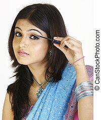 Beautiful girl putting on mascara