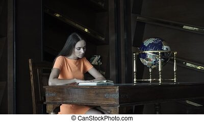 Beautiful girl reading a book in the library 4K