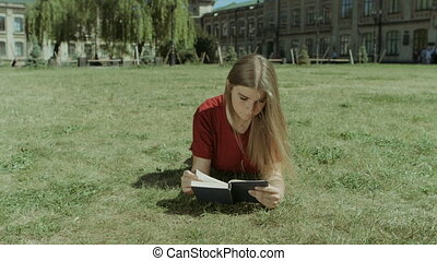 Beautiful girl reading a book on campus lawn