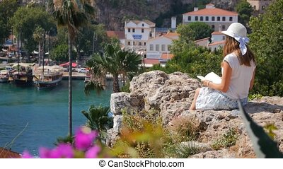 Beautiful girl reading a book on the rocks