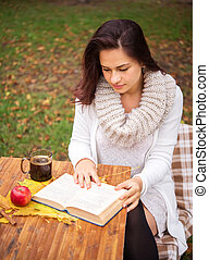 girl reading a book outside in autumn