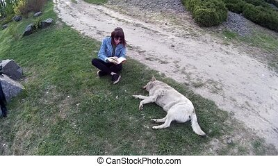 Beautiful girl reading a book to a stray dog 2