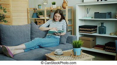 Beautiful girl reading book turning pages relaxing on sofa...