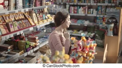 Beautiful woman in casual clothing carefully reading product contents while doing shopping in local market. Female with dark hair choosing fresh goods to buy at grocery store.