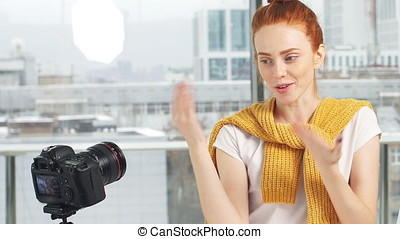 Beautiful girl recording video on camera at office. Fashion blogger concept.