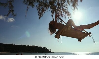Beautiful girl relax on the swing at the beach. Woman in a bikini of the tropical ocean. slow motion. 1920x1080