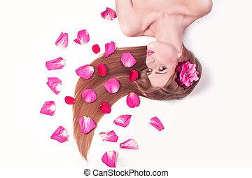 beautiful girl relaxarea ,lying among rose petals