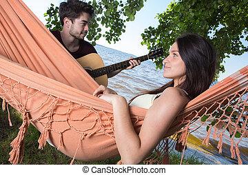 beautiful girl relaxing in hammock listening her boyfriend playing guitar