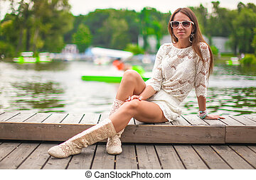 Beautiful girl relaxing in the park at warm summer day