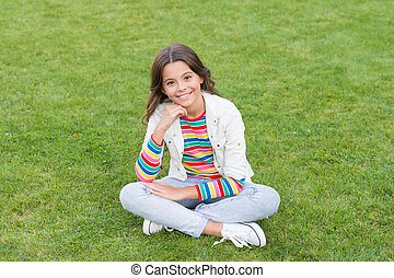Beautiful girl relaxing on grass. having rest in summer park. concept of rest and relaxation. spring nature enjoyment. cute girl resting on fresh spring grass. kid relaxing on the grass
