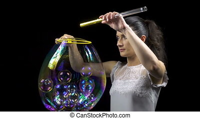 Beautiful girl releasing soap bubbles