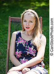beautiful girl resting, sitting in a wooden lounge chair