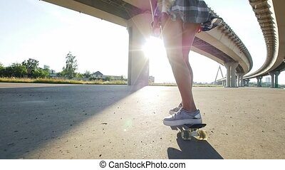 Beautiful girl rides a skateboard, in the frame slender...