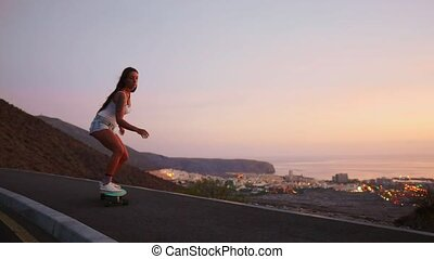Beautiful girl rides a skateboard on the road against the sunset sky