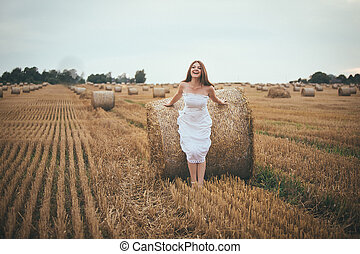 Beautiful Girl Running in the Field with a Bales of Hay -...