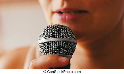 Beautiful girl say something in a hand-held microphone - A...