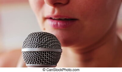 Beautiful girl says something in a hand-held microphone - A...