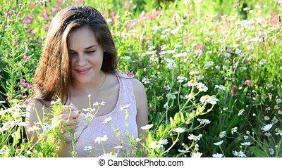 Beautiful girl sees daisies in meadow in summer