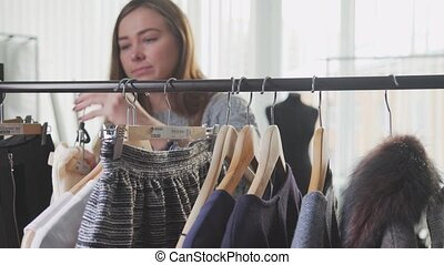 Beautiful girl shopping for clothes and shirt in fashion store.