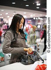 Beautiful girl shopping in a store. Shallow DOF.