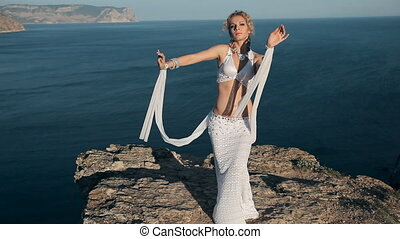 Beautiful girl shows all the beauty of oriental dance standing on a mountain in Crimea