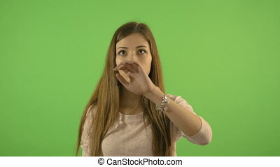 Beautiful girl shows gestures on imaginary screen. Looks and searches for information. On the background of a green screen.