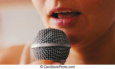 Beautiful girl sing something in a hand-held microphone - A...